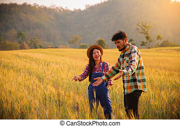 Two farmers man and woman standing in a wheat field watching the sunset.