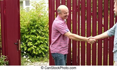 two farmers shaking hands and talking to each other on sunny...