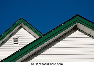 Two farmhouse roof peaks with white siding and green trim...