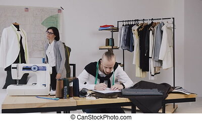 Two fashion designers working at the office with different tailoring tools sand clothes. Working on new collection together. Caucasian fashion designer and tailor