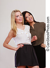 two fashion women african and caucasian posing