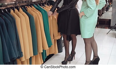Two fashionable ladies choosing the coats in shop
