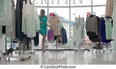 Tilt down the ladies with shopping bags strolling along clothes store in slow motion
