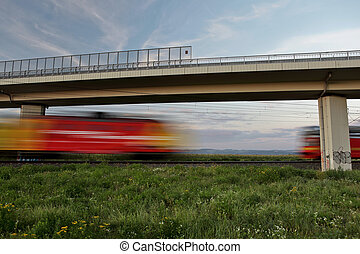 Two fast trains meeting while passing under a bridge on a...