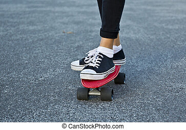 Two feet on a red skate board