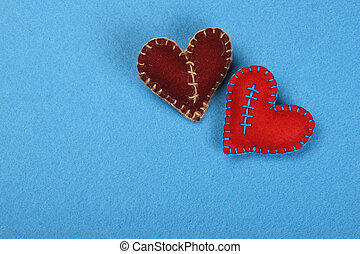 Two felt craft hearts, red and brown on blue