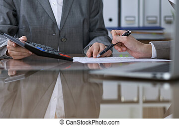 Two female accountants counting on calculator income for tax form completion, hands closeup. Internal Revenue Service inspector checking financial document. Planning budget, audit  concept