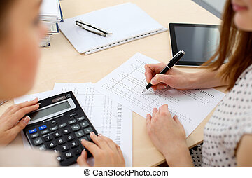 Two female accountants counting on calculator income for tax form completion hands closeup. Internal Revenue Service inspector checking financial document. Planning budget, audit  concept