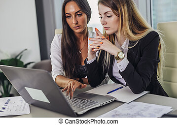 Two female accountants working together on financial report using laptop sitting at desk in account department
