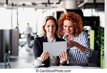 Two female business people with tablet sitting in an office, talking.