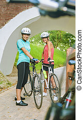 Two Female Caucasian Cyclists Standing Outdoors Smiling