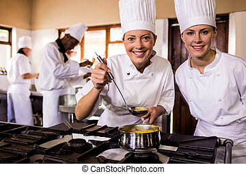 Two female chefs preparing food in kitchen