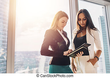 Two female colleagues with tablet computer while standing in office building
