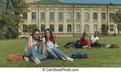Two female college friends gossiping on campus lawn -...