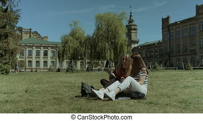 Two female college friends meeting on campus lawn