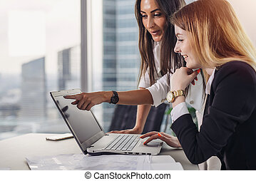 Two female coworkers pointing at laptop screen and laughing during working process in modern office
