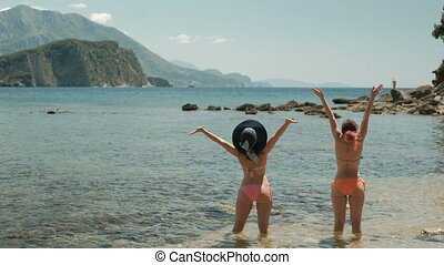 Two female figures are back on the beach with arms outstretched.