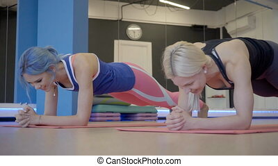 Two female friends are doing plank exercise on fitness class in the gym.