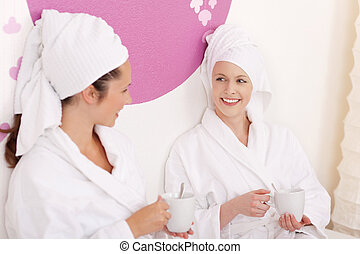 Two female friends chatting at a wellness center