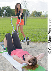 two female friends dong fitness in the park