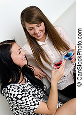 Two female friends drinking cocktail