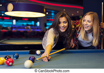 Two female friends enjoying pool game