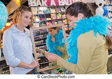 two female friends having fun while fashion shopping