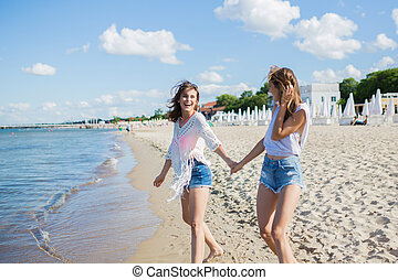 Two female friends holding hands walking on beach laughing