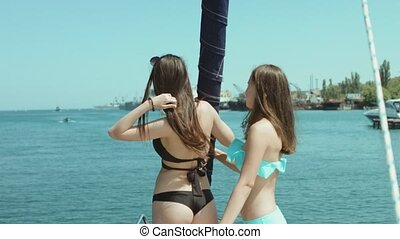 Two female friends in bikini posing on the yacht in the sea