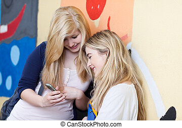 Two female friends looking at a mobile pone