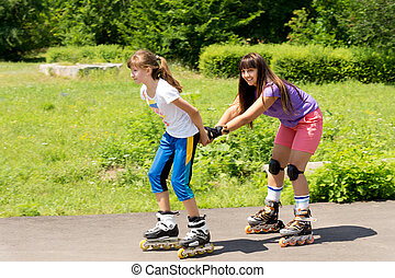 Two female friends roller skating - Two attractive teenaged...