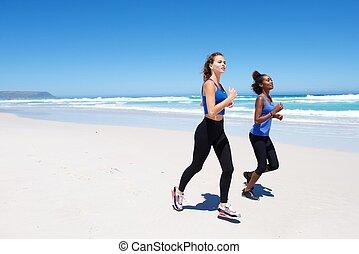 Two female friends running on beach