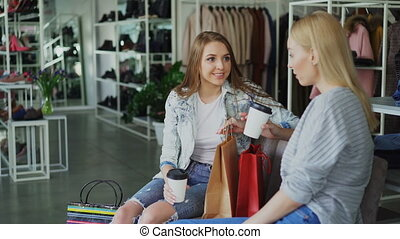 Two female friends sitting in large women's clothing shop...