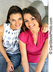Two female friends sitting on a sofa