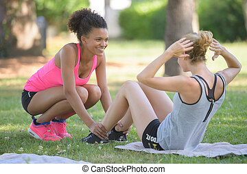 two female friends stretching at the park after jogging
