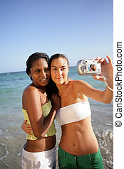 Two female friends taking self-portrait at the beach