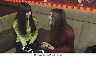 Two female friends talking in a nightclub