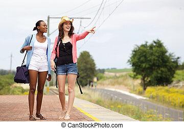 Two female friends walking on railroad station