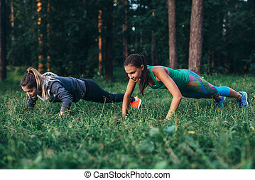 Two female friends working out together in forest doing push-up exercises on grass