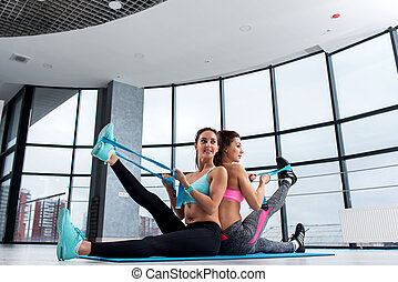 Two female friends working out together in gym sitting on mat back to back stretching leg muscles with elastic band