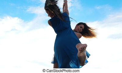 Two female gimnasts in blue dresses rotating on the pylon against the blue sky outdoors, close up