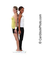 Two female gymnasts stood back to back