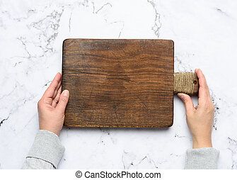 two female hands hold an empty old brown rectangular wooden cutting board