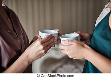 Two female hands holding a cups of coffee