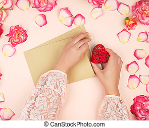 two female hands put a red heart in a brown paper envelope