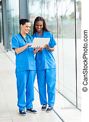 two female healthcare workers using laptop