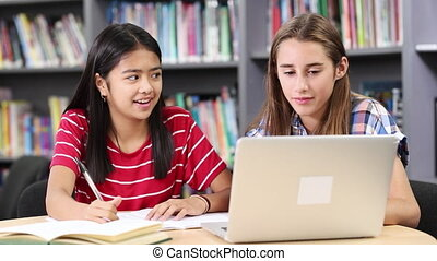 Two Female High School Students Working At Laptop In Library