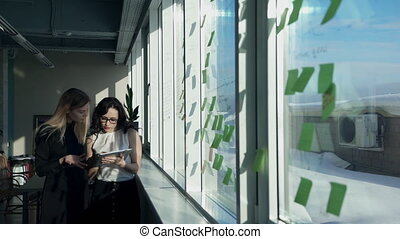 Two female office collate and recording in a computer window.