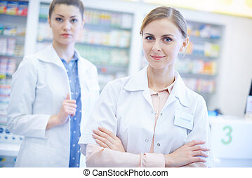 Two female pharmacists at drug store