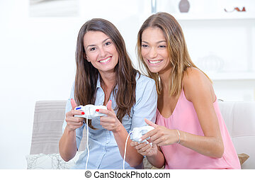 two female playing video-game in modern living room